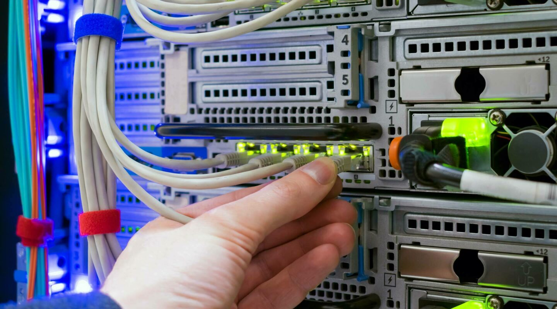 Une main branchant un câble à un serveur
