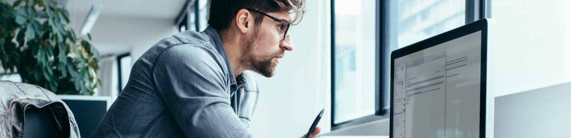 Un collaborateur consultant ses emails sur un iMac dans un open space