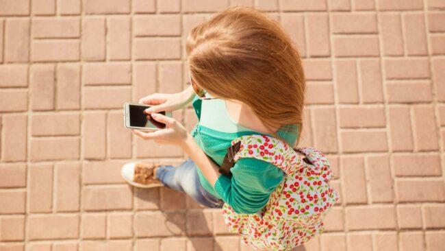 Piétonne avec smartphone en milieu urbain