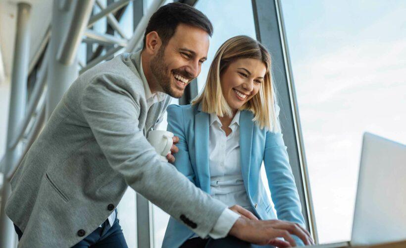 Une collaboratrice et un collaborateur devant un ordinateur et un bon petit café