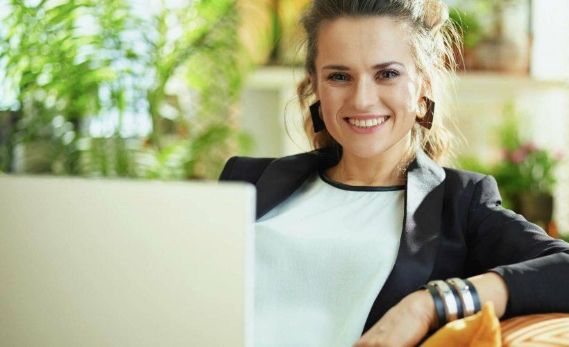 Une collaboratrice travaillant sur son ordinateur dans un divan