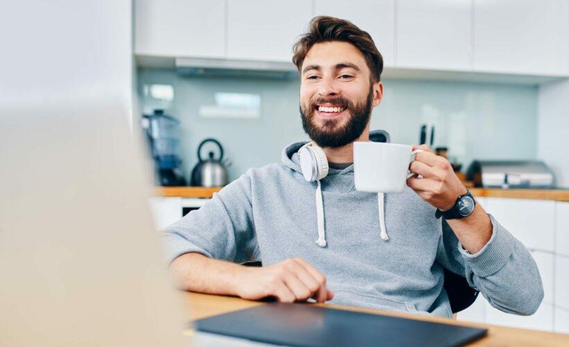 Télétravailleur buvant un café devant son ordinateur